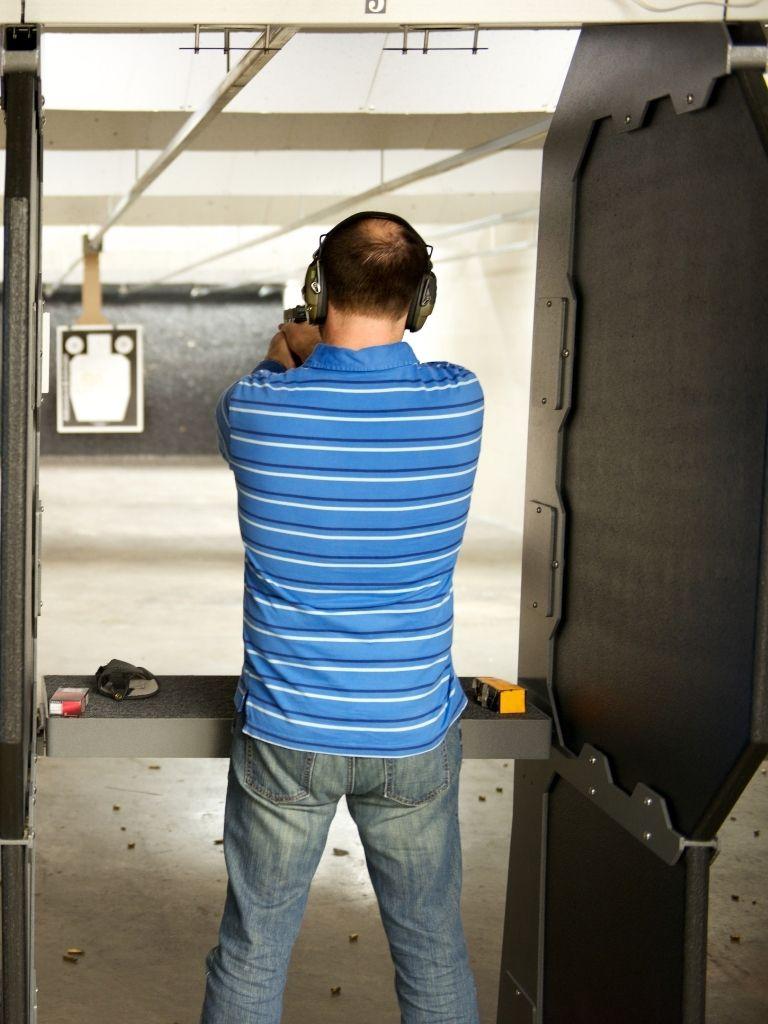 Man at gun range with bullet shell casings on the floor